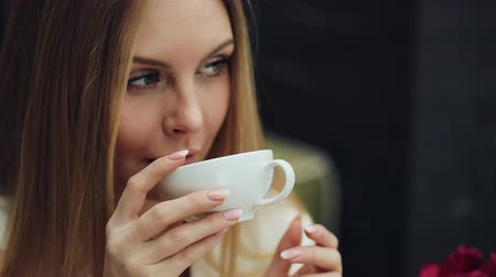 cup : Adorable young woman drinks her coffee sitting in the cafe