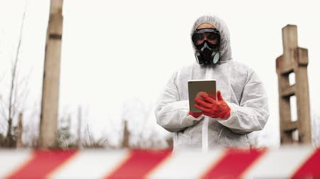 radioaktivní : Man in bio-hazard suit and gas mask takes notes in his tablet standing on the polluted land