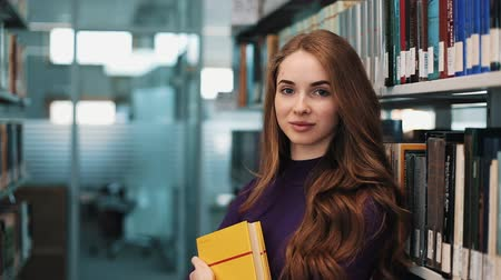 UKRAINE, LVIV - MARCH 26, 2018: Girl with long hair smiles and looks straight into the camera standing before the shelves in the library