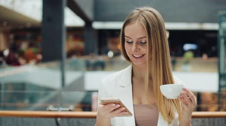 портфель : Charming young woman holds smartphone in one hand and cup of coffee in another sitting in the cafe