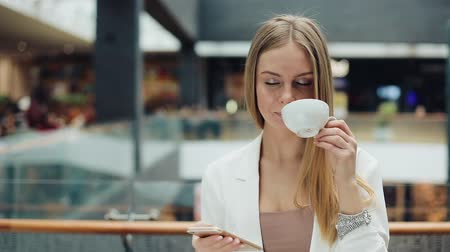 Charming young woman holds smartphone in one hand and cup of coffee in another sitting in the cafe
