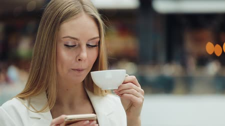 imbibe : Charming young woman holds smartphone in one hand and cup of coffee in another sitting in the cafe