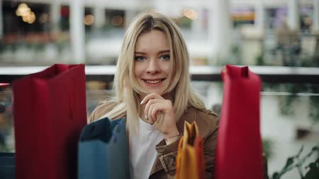 Happy blonde woman stands behind colorful shopping bags in the mall Стоковые видеозаписи