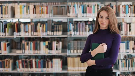 Smiling female student holds a book standing before the shelves in the library