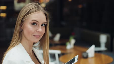 imbibe : Woman works with a tablet sitting at the table in the cafe Stock Footage