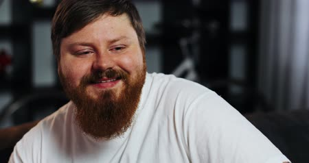 Smiling fat man with beard watches TV in the room Стоковые видеозаписи