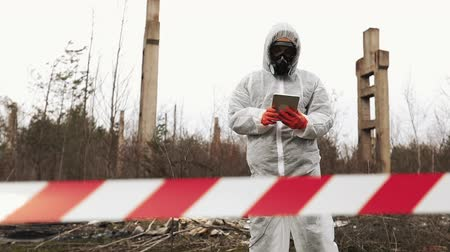 Man in bio-hazard suit and gas mask takes photos on his smartphone Стоковые видеозаписи