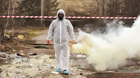 Man in bio-hazard suit and gas walks to the polluted zone covered with smoke Стоковые видеозаписи