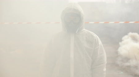 mustard : Man in bio-hazard suit and gas mask stands in the smoke Stock Footage