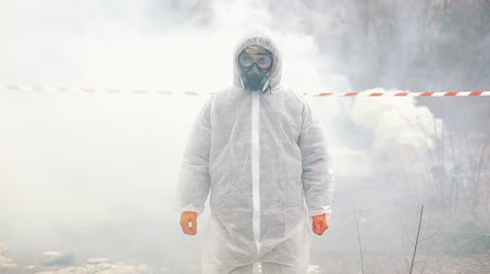 Man in bio-hazard suit and gas mask stands in the smoke Стоковые видеозаписи