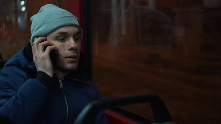 Lonely young man rides in a tram and talks on the phone in the night