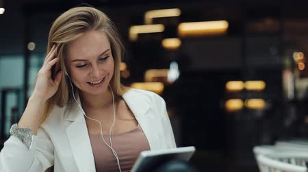 Smiling woman fixes her hair sitting in a shopping mall and reading a tablet