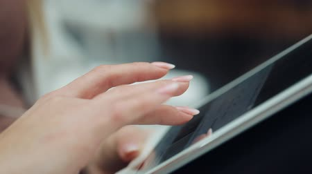 jel : Close-up of womans finger working with a tablet on her knees
