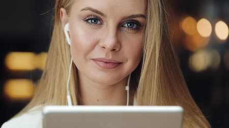 jel : Attractive young woman smiles working with a tablet in the earphones