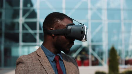 grãos : African American man plays in VR headset standing outside