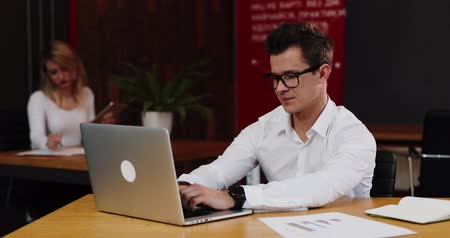 portföy : Man writes something down from his laptop working in the office Stok Video