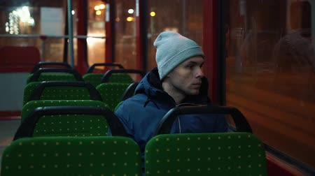 csodálkozó : Lonely young man rides in a tram in the night Stock mozgókép