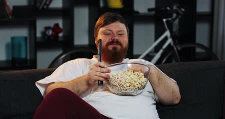 упитанность : Smiling fat man with beard watches TV in the room and eats pop-corn at the table with beer