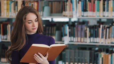 művelt : Thoughtful young female student reads a book standing in the library