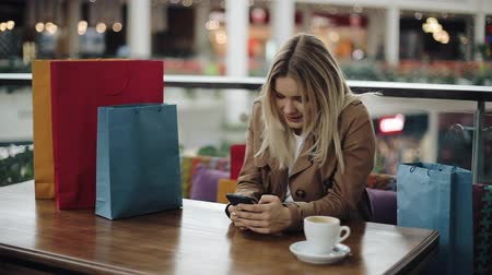 portföy : Happy blonde girl works with a smartphone at the table in cafe with shopping bags on it Stok Video