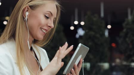 imbibe : Attractive young woman smiles working with a tablet in the earphones