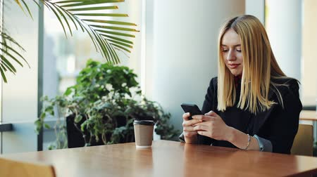 freelance work : Young blonde girl works with a smartphone sittig at the table in cafe