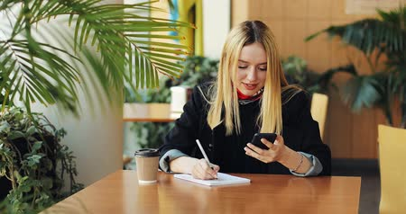 materiaŁ : Young blonde girl works with a smartphone sittig at the table in cafe. She works and drinks coffee