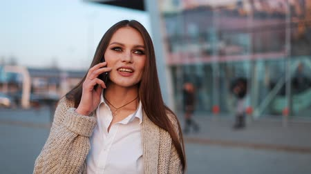 materiaŁ : Young woman with long hair walks along the street and talks on the phone