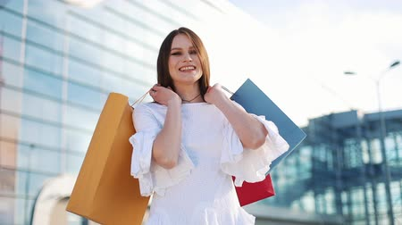imbibe : Pretty fashion model in white dress poses with shopping bags before a modern glass building