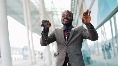 Happy african american businessman listening to music in headphones on smartphone, walking outside the office and funny dancing to the rythm. Drink coffee, funny dancing moves. Close up