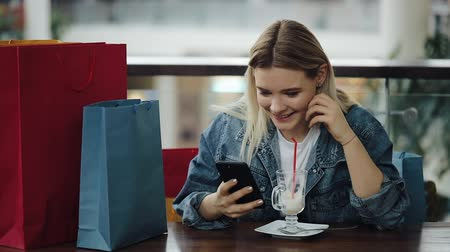 портфель : Girl checks her phone sitting with shopping bags in the cafe