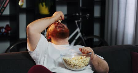 упитанность : Smiling fat man with beard watches TV in the room and eats pop-corn at the table with beer. Fat man drinks beer. Concept: Malnutrition, sedentary lifestyle, rest on the couch, obesity Стоковые видеозаписи
