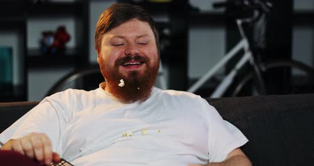 celulitida : Smiling fat man with beard watches TV in the room and eats pop-corn at the table with beer. Fat man drinks beer. Concept: Malnutrition, sedentary lifestyle, rest on the couch, obesity Dostupné videozáznamy