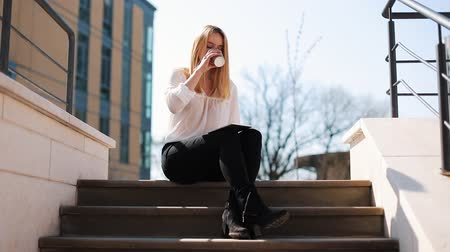 portföy : Young blonde woman works with a tablet sitting on the stairs outside and drinking coffee Stok Video