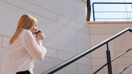 образованный : Young blonde business woman walks upstairs outside in a sunny day near office building Стоковые видеозаписи