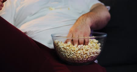 watch tv : Fat man takes pop-corn from the bowl with his hand
