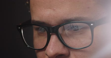 materiaŁ : Close-up of mans eyes in glasses while he works at the laptop in office