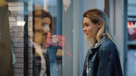 söyleme : Charmed young blonde woman stands before a show window in the shopping mall