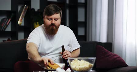 упитанность : Funny fat guy eating fast food, drink beer and doing dumbbell training. He is sitting at home on the couch in front of the TV. Concept of malnutrition, sport, obesity Стоковые видеозаписи