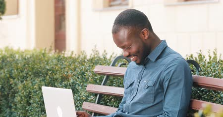 кулак : Attractive African American man working on laptop computer sits on the bench. Received good news excited and happy. Remote freelance work. Success concept Стоковые видеозаписи