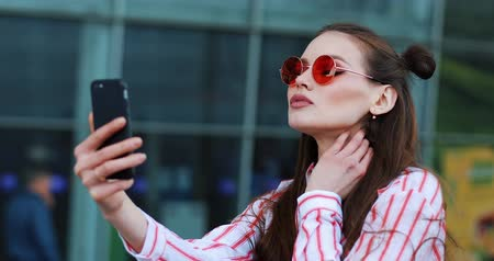 materiaŁ : Pretty young model in red sunglasses takes a selfie on her smartphone