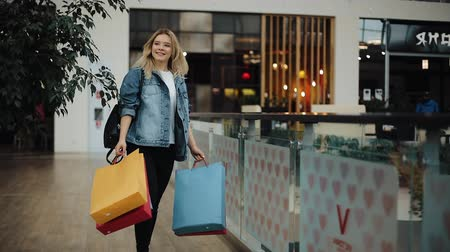 imbibe : Young blonde woman in jeans jacket walks around a shopping mall with colorful bags