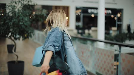 imbibe : Charming blonde girl in jeans jacket whirls with shopping bags in the mall
