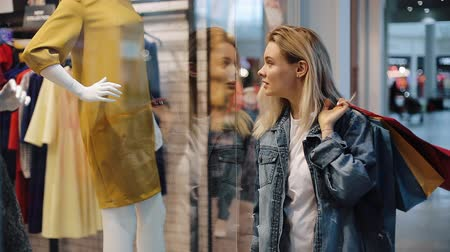 портфель : Charmed young blonde woman walks along a show window with bags in the shopping mall Стоковые видеозаписи