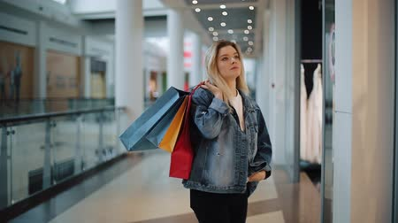 потребитель : Thoughtful young blonde woman walks along a show window with bags in the shopping mall