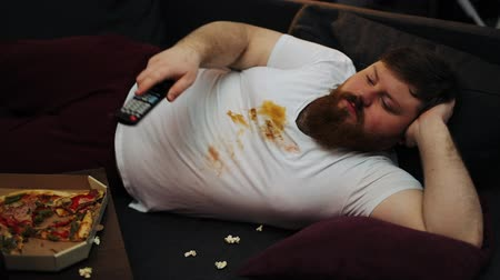 упитанность : Fat man in dirty T-shirt laughs watching the TV-set on his couch in a living room