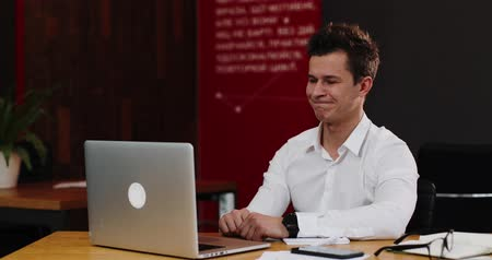 grão : Man talks on the video-call on his laptop in the office. Young attractive businessman in a white shirt showing fuck you o after the video call