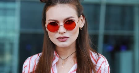 imbibe : Pretty fashion in red sunglasses poses to the camera with before a modern glass building. A young transgender looking into the camera
