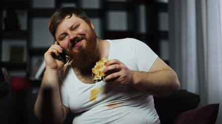 celulitida : Dirty fat bearded man talks on the smartphone, eating a burger and drinking beer sitting on the couch. Concept of malnutrition, food delivery, communication and obesity