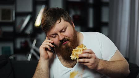 bel ölçüsü : Dirty fat bearded man talks on the smartphone, eating a burger and drinking beer sitting on the couch. Concept of malnutrition, food delivery, communication and obesity